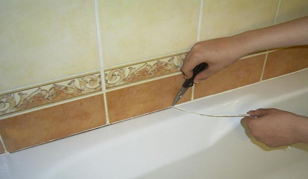 удаление лишней затирки из стыка между ванной и стеной