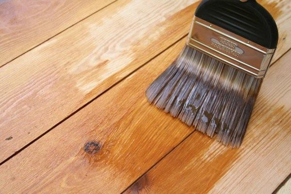 процесс грунтовки деревянного пола кистью