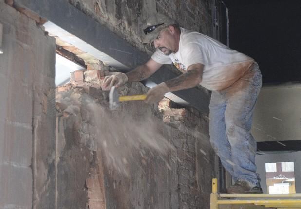 Мужчина сносит стену молотком