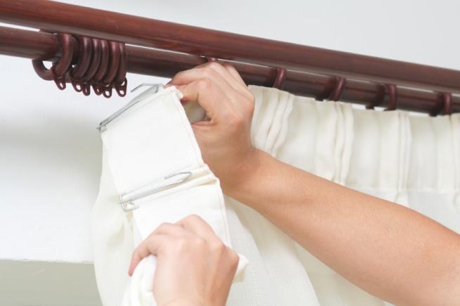 Женщина вешает шторы на карниз