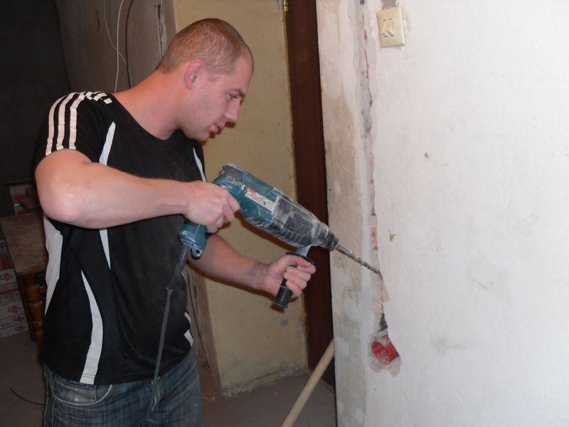 Мужчина проводит электрику в гараже