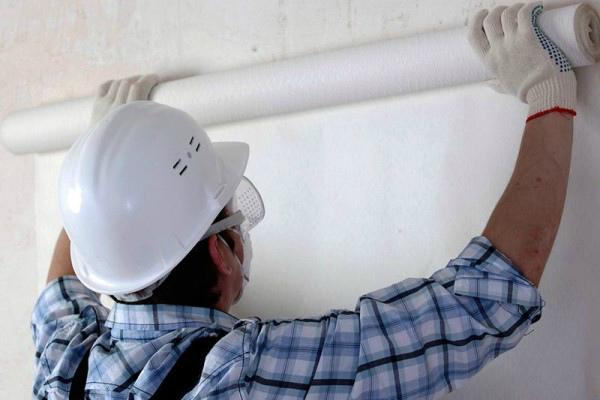 Прикрепление стеклообоев на смазанную клеем стену